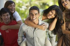 South American men giving girlfriends piggyback rides - stock photo