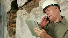 Construction worker on phone and using a tablet pc Stock Footage