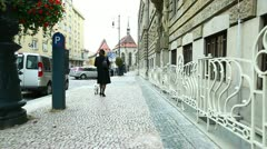 Woman in black coat walk with dog at prague street Stock Footage