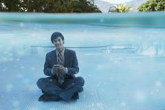 South American businessman in swimming pool - stock photo