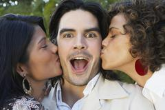 Two women kissing man on cheek - stock photo