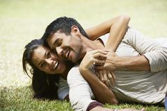 South American couple laying in grass - stock photo
