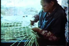 Maori women working on making grass skirts, medium wide shot Stock Footage