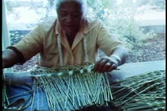 Maori woman working on making grass skirts, close up - stock footage