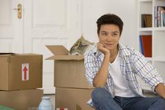Asian man next to unpack moving boxes Stock Photos