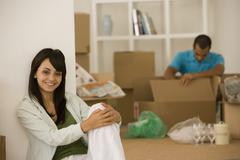 Young couple unpacking boxes in new house - stock photo