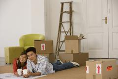 Asian couple on floor next to moving boxes Stock Photos