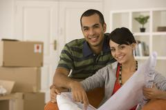 Young couple looking at blueprints in new house - stock photo