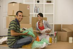 Stock Photo of Young couple packing moving boxes