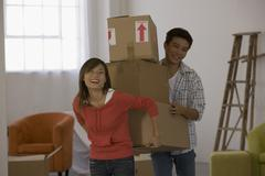 Asian couple carrying moving boxes Stock Photos