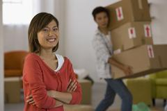 Asian woman laughing while husband carries boxes Stock Photos