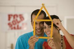 Couple holding folding ruler shaped like house Stock Photos