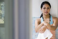 Stock Photo of Young woman sitting against tile wall
