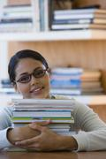 Young woman with stack of books Stock Photos