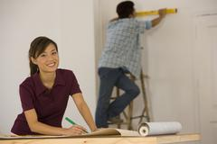 Asian couple hanging wall paper - stock photo