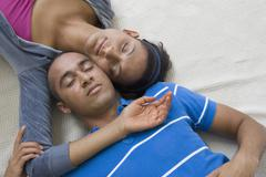 Young couple laying with heads touching Stock Photos