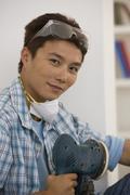 Asian man holding power sander Stock Photos