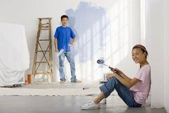 Asian couple painting interior of house - stock photo
