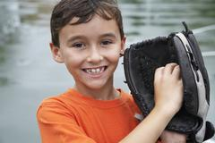Boy wearing baseball mitt - stock photo