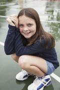 Stock Photo of Girl crouching on playground
