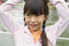 Stock Photo of Asian girl with hands on head