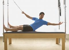 Asian man stretching on exercise equipment Stock Photos