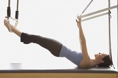 Woman stretching on exercise equipment - stock photo