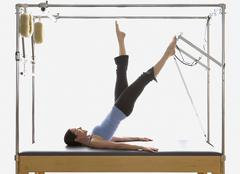 Woman stretching on exercise equipment Stock Photos