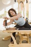 Senior woman stretching on exercise equipment Stock Photos