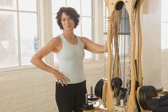 Senior woman standing next to exercise equipment - stock photo