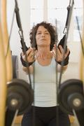 Senior woman stretching on exercise equipment - stock photo