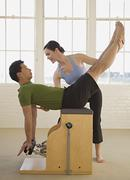 Instructor helping man in exercise studio Stock Photos