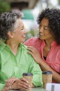 African American mother and adult daughter smiling at each other Stock Photos