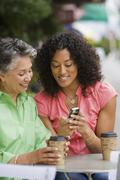 African American mother and adult daughter looking at cell phone - stock photo