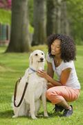 African American woman petting dog - stock photo