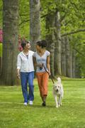 African American mother and adult daughter walking dog - stock photo