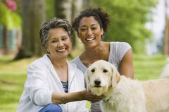 African American mother and adult daughter petting dog - stock photo
