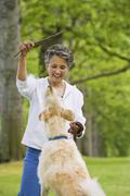 African American woman playing with dog - stock photo
