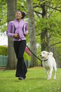 African American woman jogging with dog Stock Photos