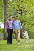 African American mother and adult daughter walking dog Stock Photos