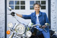Senior African American woman sitting on motorcycle - stock photo