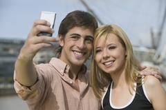 Multi-ethnic couple taking own photograph Stock Photos