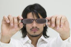 Stock Photo of Young Hispanic man holding eyeglasses