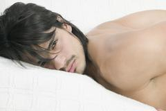 Young Hispanic laying on bed - stock photo