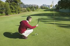 Hispanic man playing golf Stock Photos