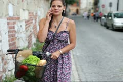 Happy woman with bicycle talking on mobilephone Stock Footage