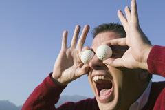 Latinalaisamerikkalainen mies tilalla golfpallot silmien yläpuolella Kuvituskuvat