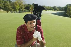 Hispanic man holding golf club Stock Photos