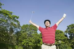 Hispanic man cheering with golf club Stock Photos