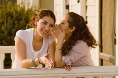 Hispanic women telling secret Stock Photos